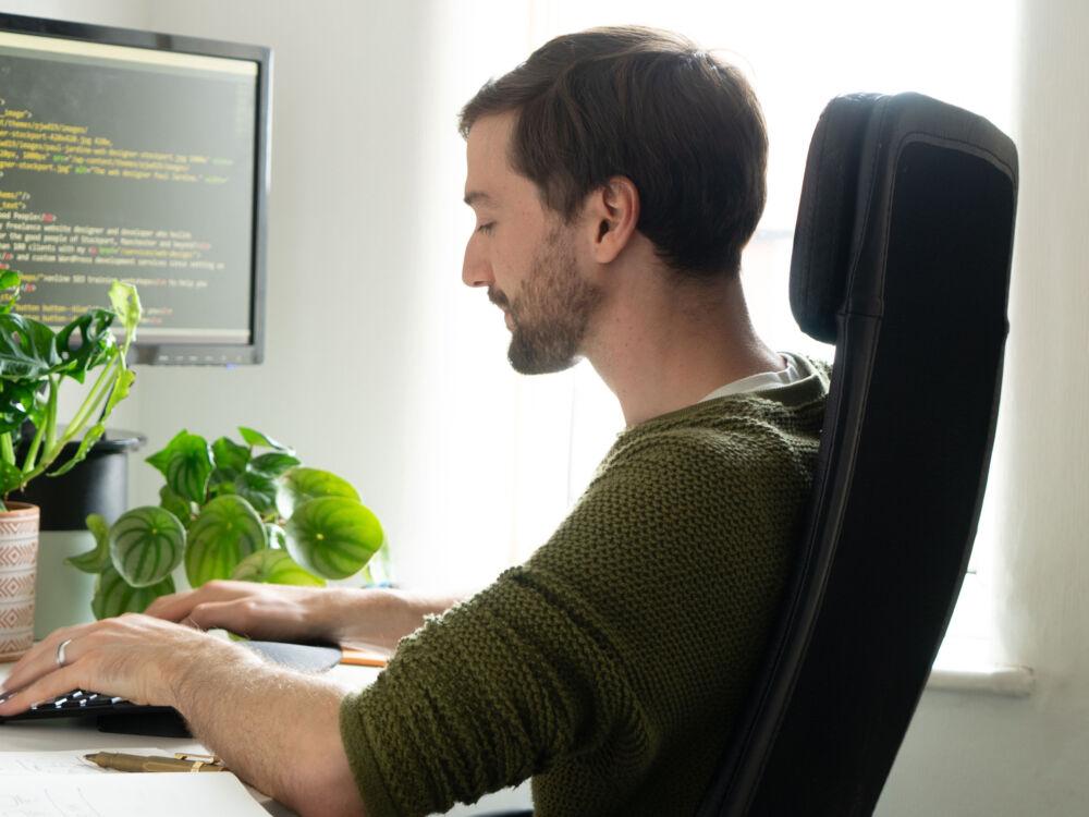 The web designer Paul Jardine working at his desk writing HTML code.
