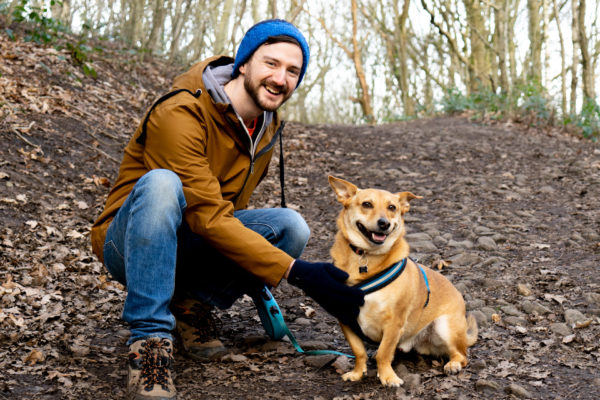 The web designer Paul Jardine and his dog Bo walking in a forest.