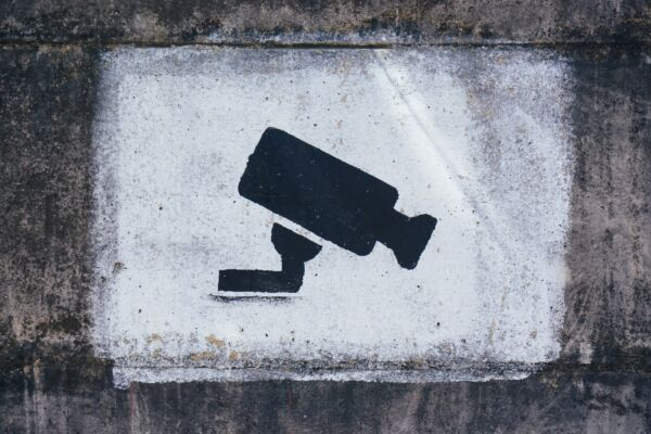 Spray painted artwork of a security camera on a wall.