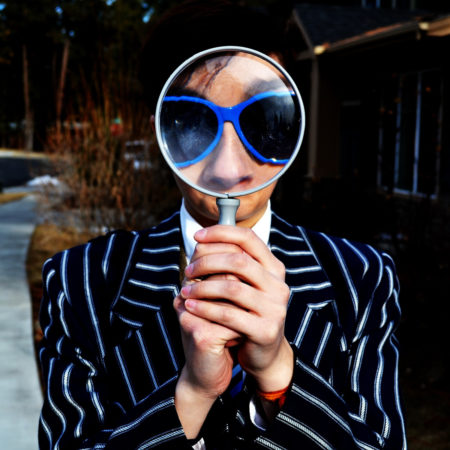 Man in a striped suit looking through a magnifying glass.