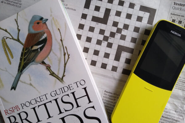 A montage of a book of birds, an old Nokia mobile phone and a newspaper crossword.
