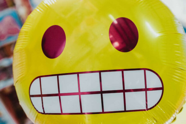 Helium balloon of a stressed face emoji.